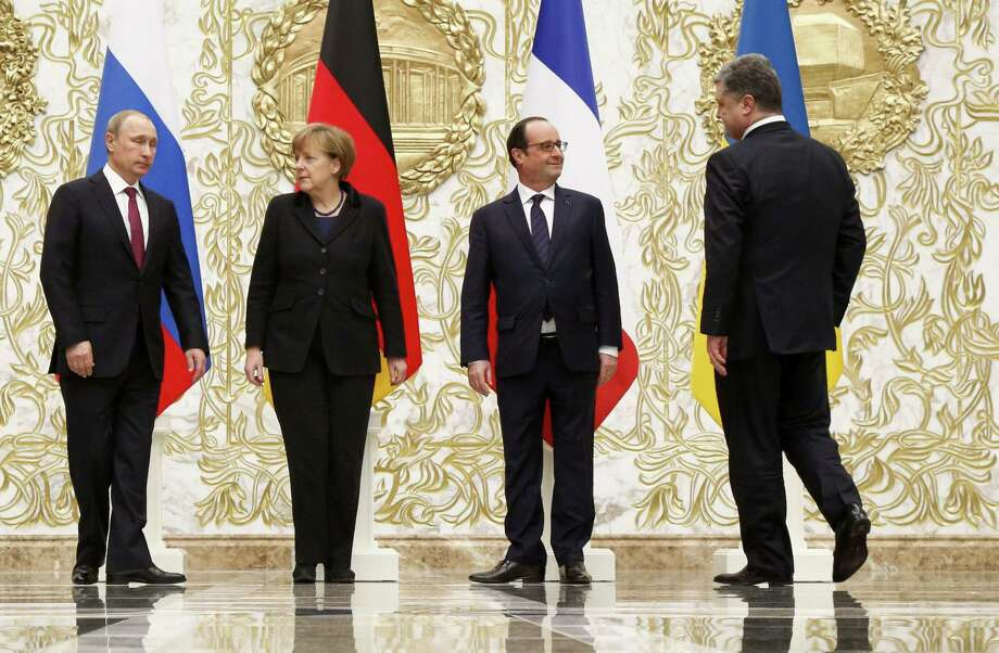 From the left : Russian President Vladimir Putin, German Chancellor Angela Merkel, French President Francois Hollande, and Ukrainian President Petro Poroshenko arrive to pose for a photo during a time-break in their peace talks in Minsk, Belarus, Wednesday, Feb. 11, 2015. Leaders of Russia, Ukraine, France and Germany are gathering for crucial talks in the hope of negotiating an end fighting between Russia-backed separatist and government forces in eastern Ukraine. (AP Photo/Alexander Zemlianichenko) Photo: AP / AP