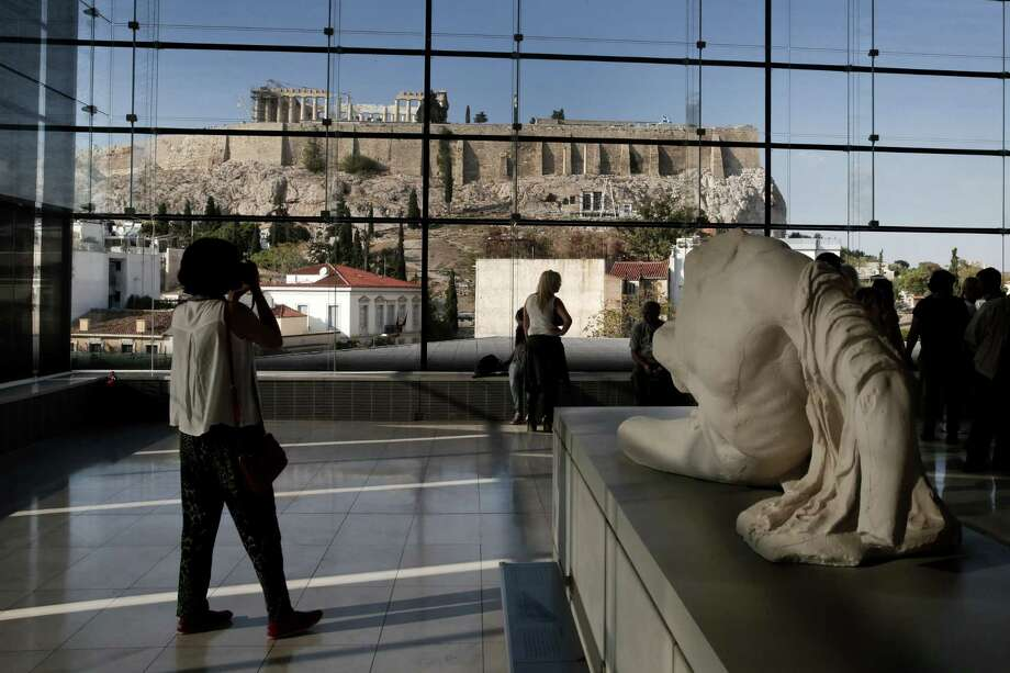 Visitors to Athens' Acropolis Museum look at the vista to the ancient Temple of Parthenon, Sunday, Oct. 12, 2014. Lawyers Geoffrey Robertson and Amal Alamuddin arrive Monday on a four-day visit to meet government officials, including Prime Minister Antonis Samaras, and advise on Greece's quest to have the parts of Parthenon currently displayed at London's British Museum returned to Athens. Alamuddin's husband, actor George Clooney, campaigned for the Parthenon Marbles' return when promoting his film The Monuments Men. Photo:  (AP Photo/Petros Giannakouris)  / AP