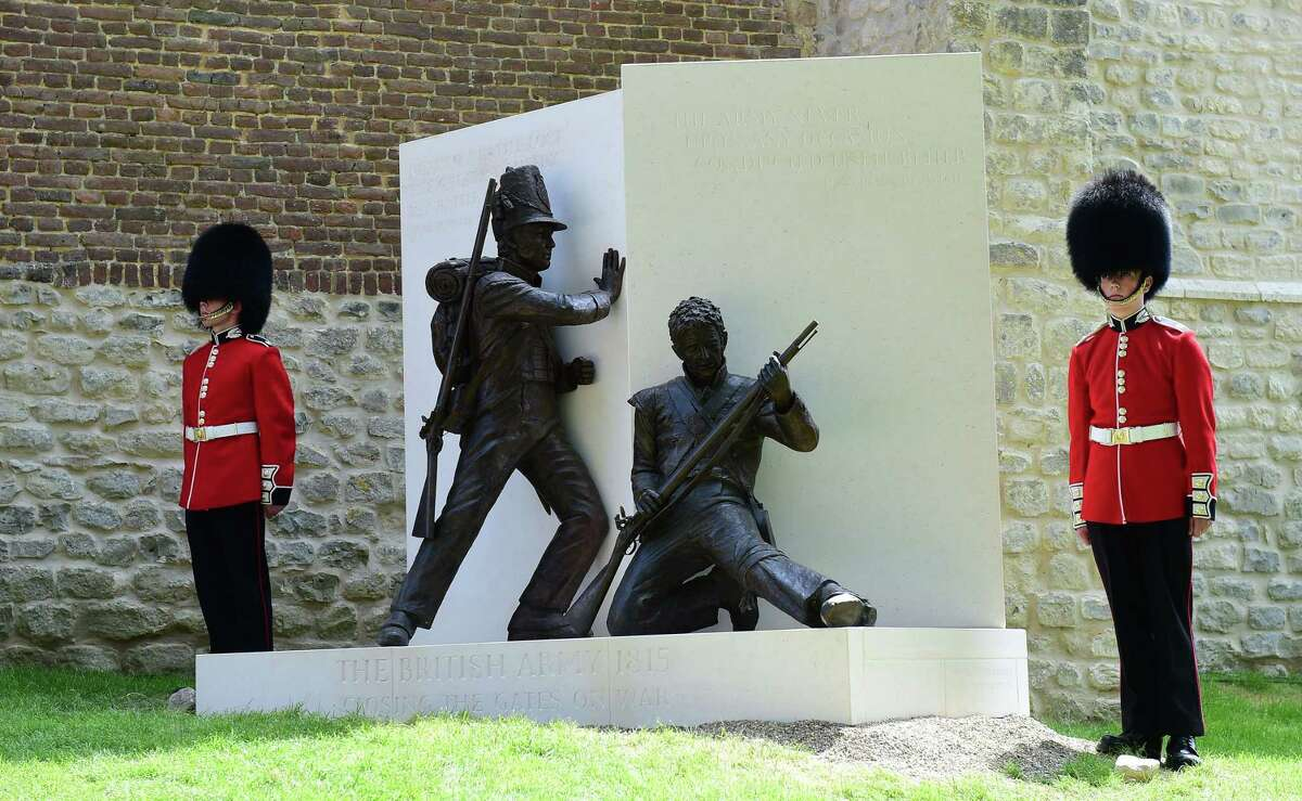 Guards stand on either side of a newly unveiled memorial during the ceremonial opening of Hougoumont Farm in Braine-l'Alleud, near Waterloo, Belgium on Wednesday, June 17, 2015. Hougoumont Farm played a critical role in the outcome of the Battle of Waterloo, and the newly restored farm will open to the general public on June 18, 2015. (AP Photo/Emmanuel Dunand/Pool Photo via AP)