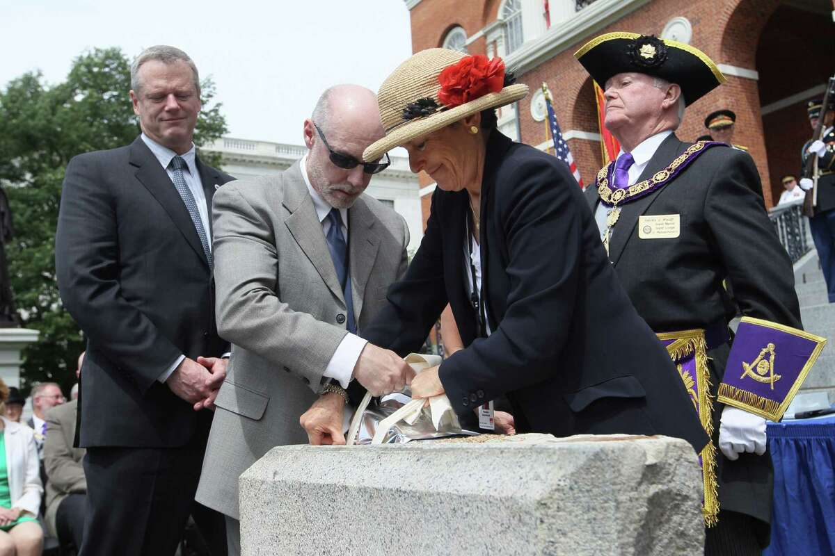 Massachusetts Gov. Charlie Baker, left, watches as State Arcivist Michael Comeau amd MFA head of Objects Conservation Pamela Hatchfield lower the time capsule into the cornerstone during a ceremony at the Statehouse in Boston, Wednesday, June 17, 2015. At right, is Grand Master of Grand Lodge of Masons Harvey Waugh. The time capsule was returned to cornerstone during ceremony at the Statehouse steps. A a set of 2015 U.S. mint coins and a silver plaque added to its contents for a future generation to discover. (Joanne Rathe/The Boston Globe via AP, Pool)
