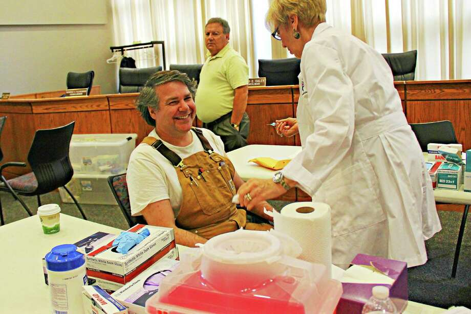 Middletown resident Scott Williams gets his annual flu shot at a clinic held by the city on Tuesday. More than 40 people stopped by for innoculation before noon. Photo: Kathleen Schassler — Middletown Press   / Kathleen Schassler All Rights