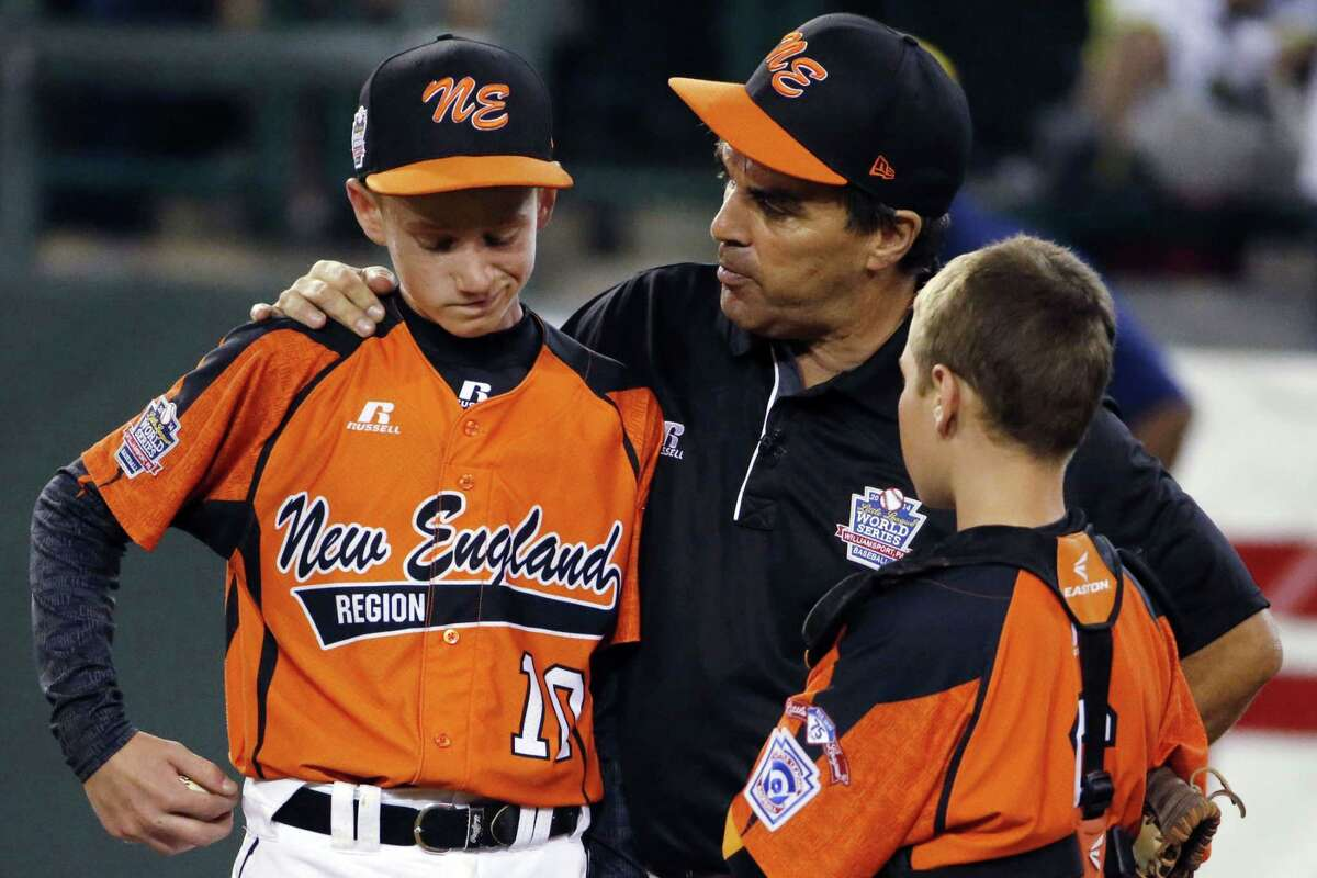 In this Aug. 18, 2014 file photo, Cumberland manager David Belisle talks with pitcher CJ Davock, left, and catcher Trey Bourque during the fifth inning of an elimination game against Chicago at the Little League World Series in South Williamsport, Pa. Chicago won 8-7. It was announced Wednesday that the Chicago team was stripped of its national title for using players from outside league boundaries. Belisle said Cumberland got beat by cheaters and the adults who orchestrated the scheme should be ashamed.