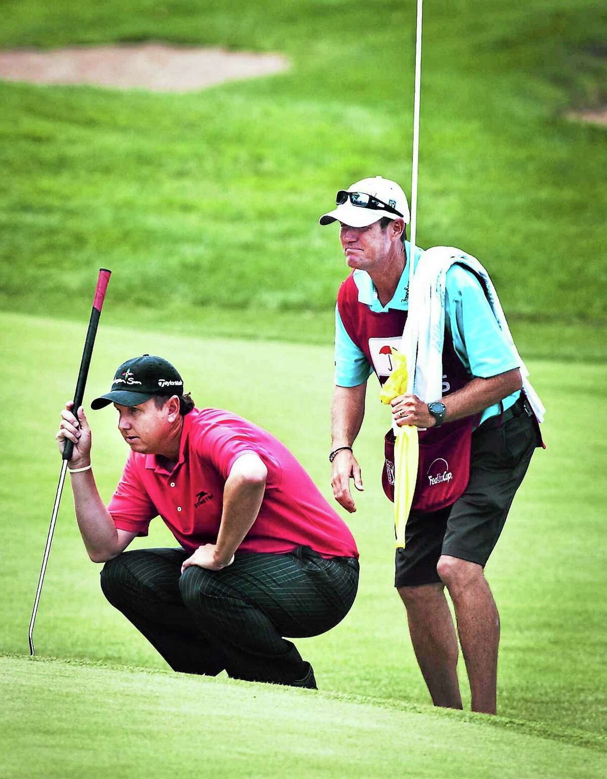 J.J. Henry and his caddie line up a putt on the 17th hole at last year's Travelers Championship.