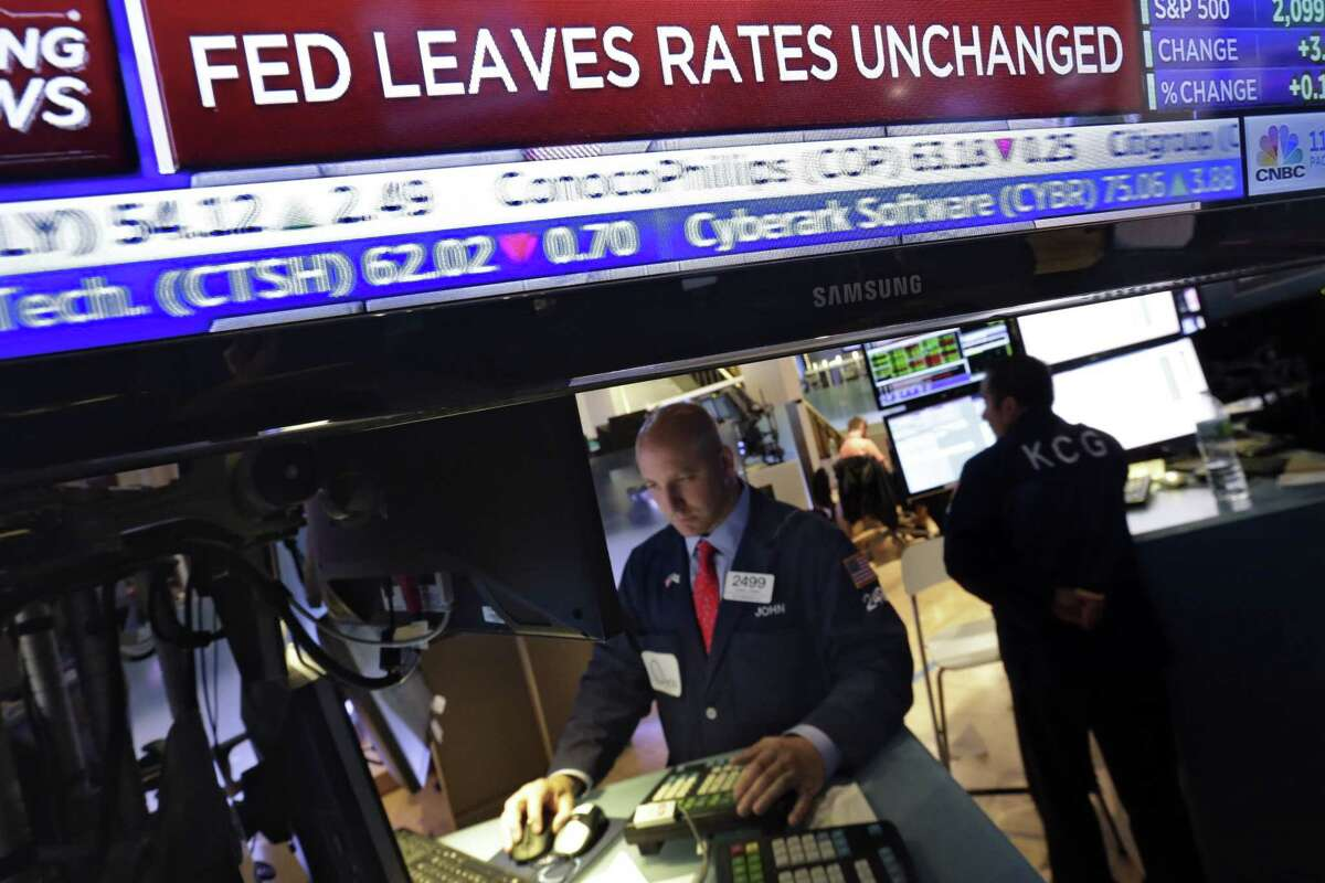 A television screen at the trading post of specialist John Parisi, left, on the floor of the New York Stock Exchange, shows the decision of the Federal Reserve Wednesday.