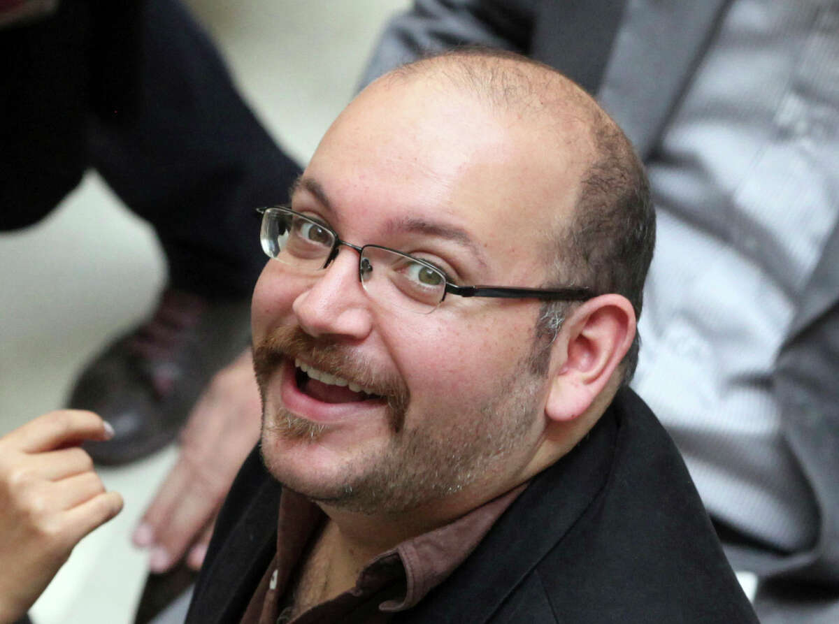 In this April 11, 2013 photo, Jason Rezaian, an Iranian-American correspondent for the Washington Post, smiles as he attends a presidential campaign of President Hassan Rouhani in Tehran, Iran. Iran's official IRNA news agency reported that the verdict against Rezaian has been issued. Rezaian, the Post's Tehran bureau chief, is accused of charges including espionage in a closed-door trial that has been widely criticized by the U.S. government and press freedom organizations.
