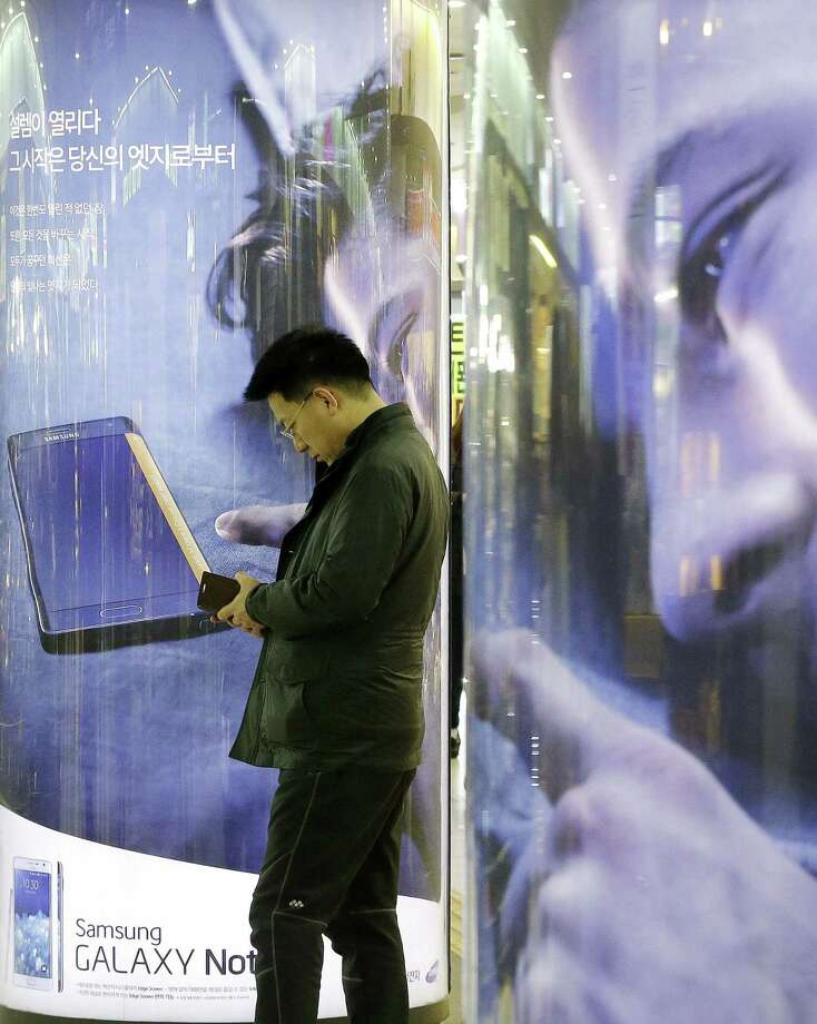 A man uses his smartphone in front of advertisements for Samsung Electronics' Galaxy Note Edge at a subway station in Seoul, South Korea on Jan. 29, 2015. Photo: AP Photo/Ahn Young-joon  / AP