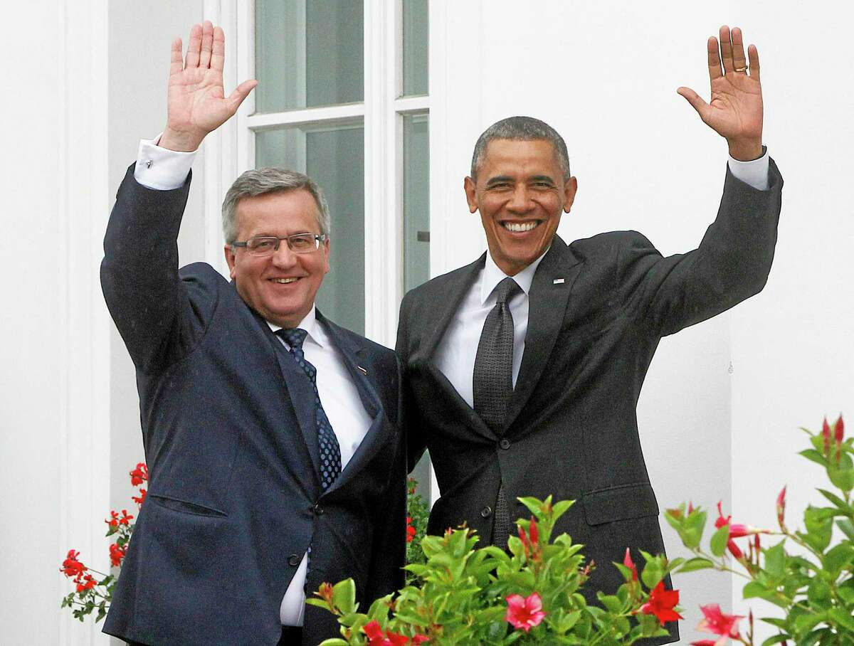 U.S. President Barack Obama,right, and Poland's President Bronislaw Komorowski ,left, wave wave at Belveder residence in Warsaw, Poland, on Tuesday June 3, 2014.Obama came to Poland to meet regional leaders and attend ceremonies marking 25 years of Poland's democracy. (AP Photo/Czarek Sokolowski)