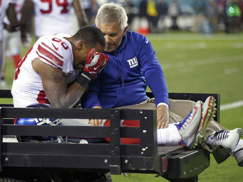 Giants wide receiver Victor Cruz, left, is carted off the field on Sunday. Photo: The Associated Press  / AP