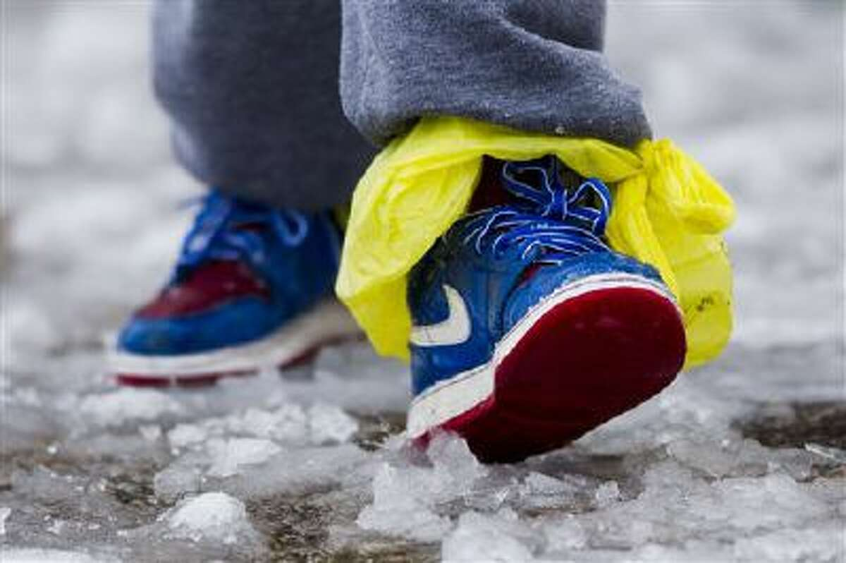 A young boy walks through slush with his sneakers lined with plastic bags, Thursday, Feb. 13, 2014, in Philadelphia. Snow and sleet are falling on the East Coast, from North Carolina to New England, a day after sleet, snow and ice bombarded the Southeast. (AP Photo/Matt Rourke)