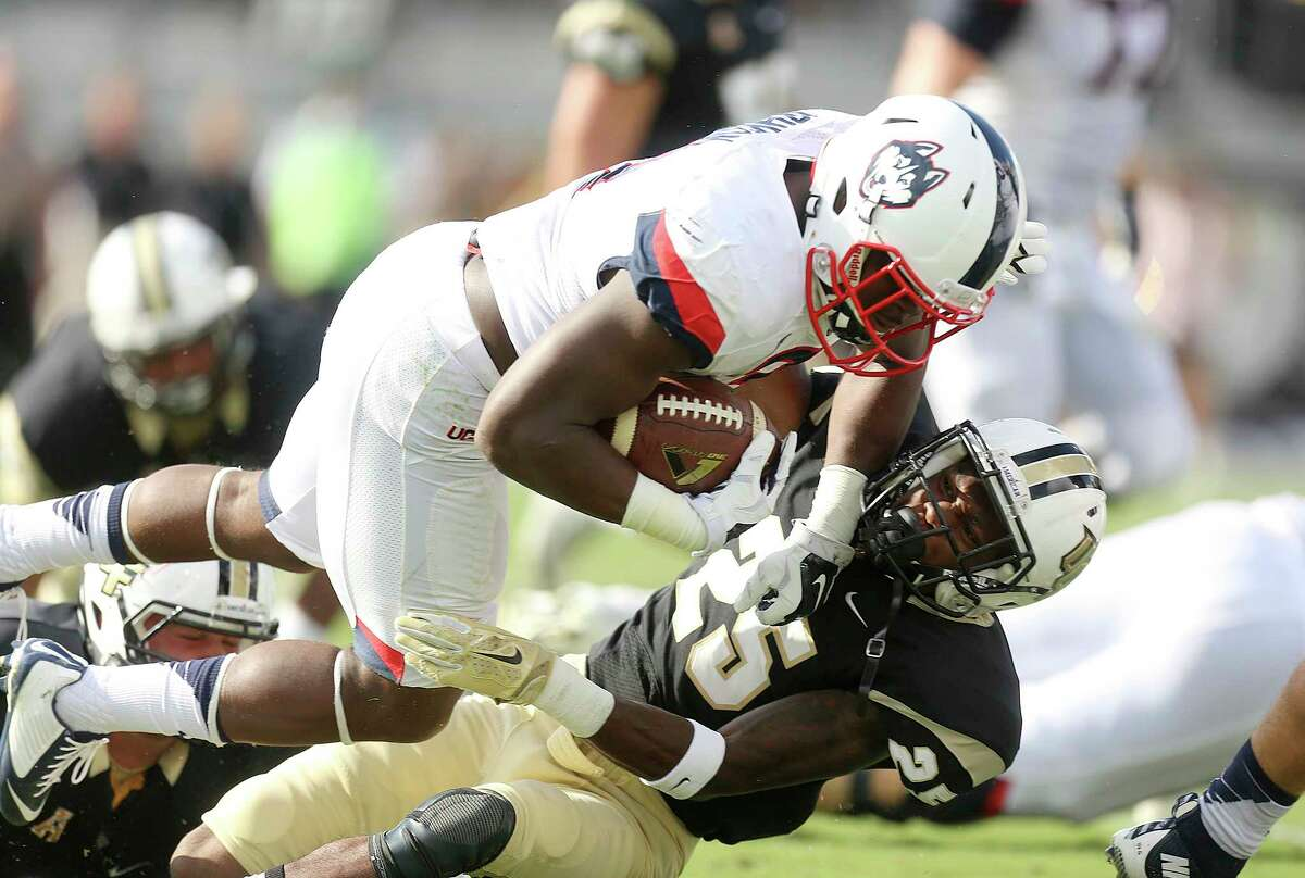 UConn's Ron Johnson runs over a UCF defender during Saturday's game.