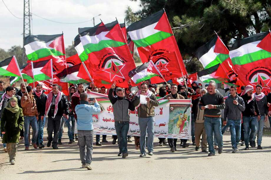 Palestinian supporters of the Democratic Front for the Liberation of Palestine, march in an area near the West Bank village of Tourah west of Jenin, Saturday, Feb. 15, 2014. Dozens of Palestinians held a march to protest against the Palestinian-Israeli peace talks and U.S. Secretary of State John Kerry's peace efforts. Later on some of the protesters started throwing stones at a nearby gate of the separation wall, and Israeli soldiers responded to halt it. (AP Photo/Mohammed Ballas) Photo: AP / AP