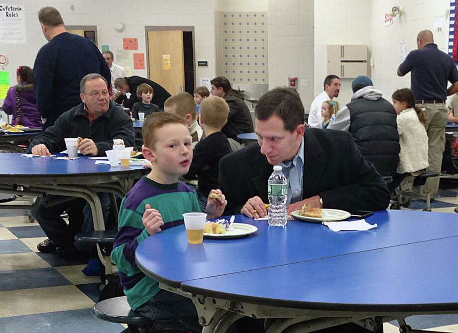 The monthly All Pros Dads breakfasts at Bielefield Elementary School in Middletown, one of which is shown in this archive photograph, provide a way for fathers and their children to connect and talk about things they may not at home. The program is now offered at Farm Hill School. Photo: File Photo