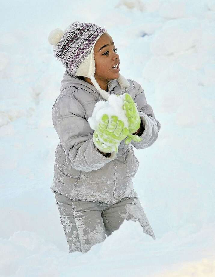 Six-year-old Maya Gunn of Middletown gets ready to fire a snowball at her brother while playing in their front yard in this archive photo. Photo: File Photo  / TheMiddletownPress