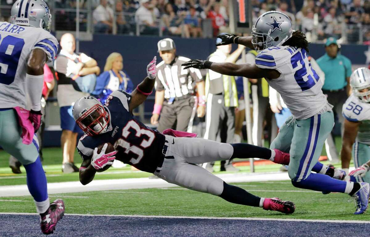 The Patriots' Dion Lewis (33) dives to score a touchdown during the second half Sunday against the Cowboys.