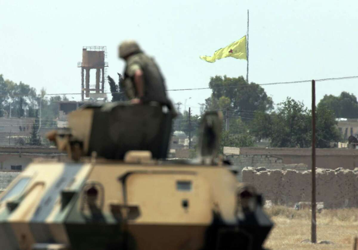 In this photo taken from the Turkish side of the border between Turkey and Syria, in Akcakale, southeastern Turkey, a Turkish soldier on an armoured personnel carrier watches as in the background a flag of the Kurdish People's Protection Units, or YPG, is raised over the city of Tal Abyad, Syria on June 16, 2015. Kurdish fighters with the YPG, captured large parts of the strategic border town of Tal Abyad from the Islamic State group Monday, dealing a huge blow to the group which lost a key supply line for its nearby de facto capital of Raqqa, a spokesman for the main Kurdish fighting force said.