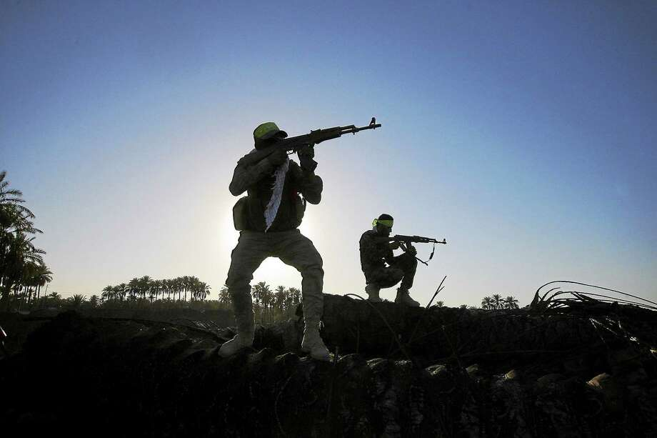 In this Oct. 7, 2014 photo, Iraqi Shiite militiamen aim their weapons during clashes with militants from the Islamic State group, in Jurf al-Sakhar, about 43 miles (70 kilometers) southwest of Baghdad, Iraq. Photo: AP Photo  / AP