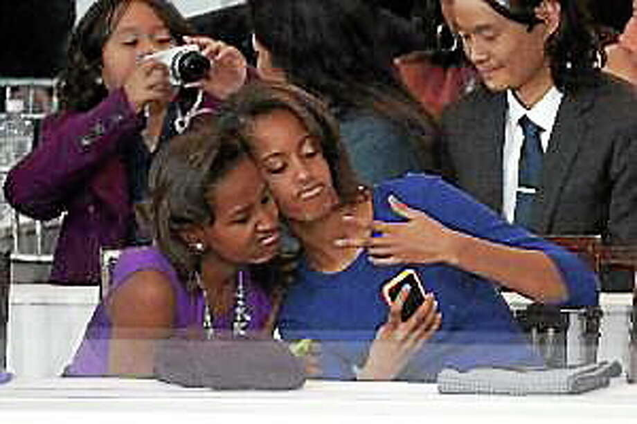 Sasha, left, and Malia Obama, daughters of U.S. President Barack Obama, take a photo of themselves during the Presidential Inaugural Parade on January 21, 2013 in Washington, D.C. Photo: (Joe Klamar — Getty Images)