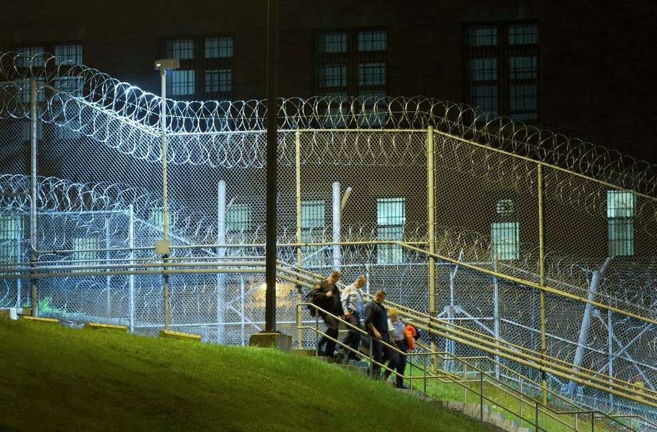 Corrections officers walk next to a fence covered in razor wire as they leave work at the Clinton Correctional Facility, Monday, June 15, 2015 in Dannemora, N.Y. State police say more than 800 law enforcement officers are pushing on in the hunt for convicted murderers David Sweat and Richard Matt 10 days after the two escaped from the maximum-security prison in rural New York. (AP Photo/Mark Lennihan) Photo: AP / AP