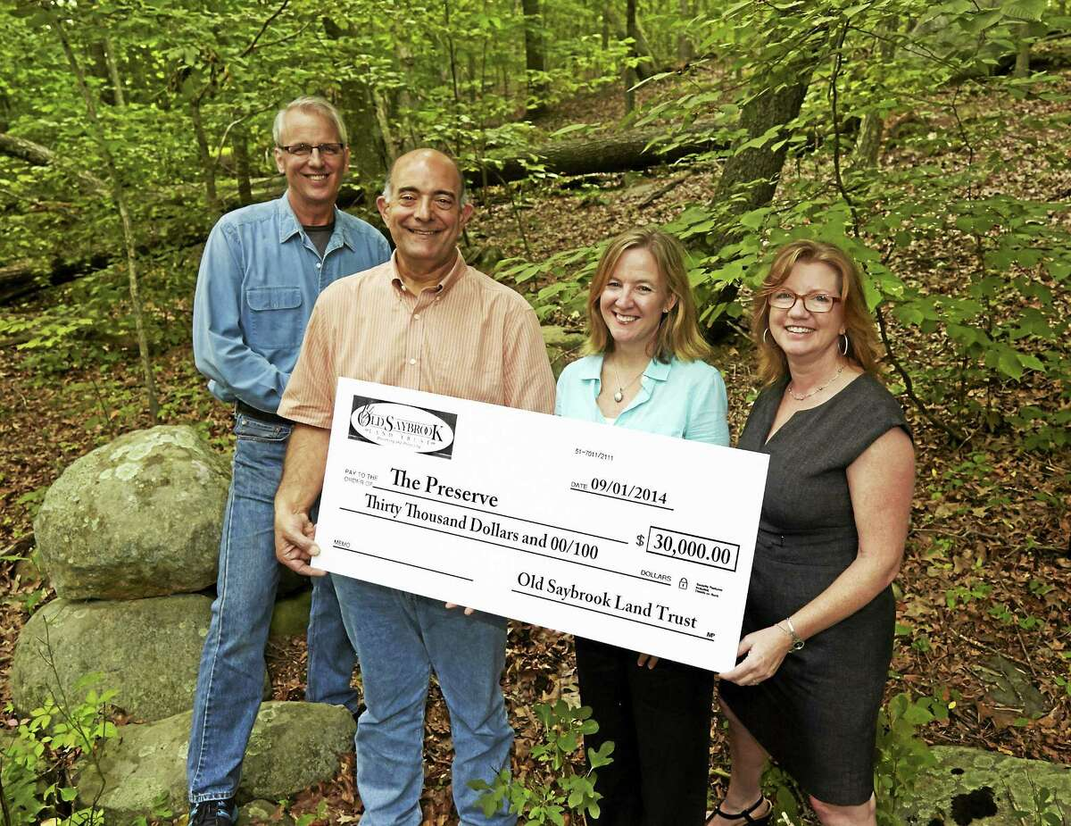 From left, Old Saybrook Land Trust President Joe Nochera and Treasurer Mike Urban present Alicia Sullivan and Lori Fernand of The Trust for Public Land showcase a check for $30,000 toward The Preserve purchase at the trailhead on Ingham Hill Road.