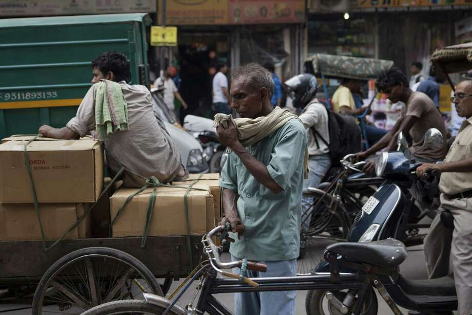 An Indian rickshaw puller pauses as he wipes sweat off his face on a hot summer day in New Delhi, India, Tuesday, June 16, 2015. High humidity prevailed in the national capital after recent showers causing discomfort to people in the city as mercury rose moderately. (AP Photo/Tsering Topgyal) Photo: AP / AP