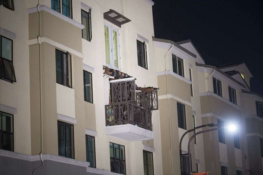 A fourth floor balcony rests on the balcony below after collapsing at the Library Gardens apartment complex in Berkeley, Calif., early Tuesday, June 16, 2015. Berkeley police say several people are dead and others injured after the balcony fell shortly before 1 a.m., near the University of California, Berkeley. Photo: AP Photo/Noah Berger  / FR34727 AP