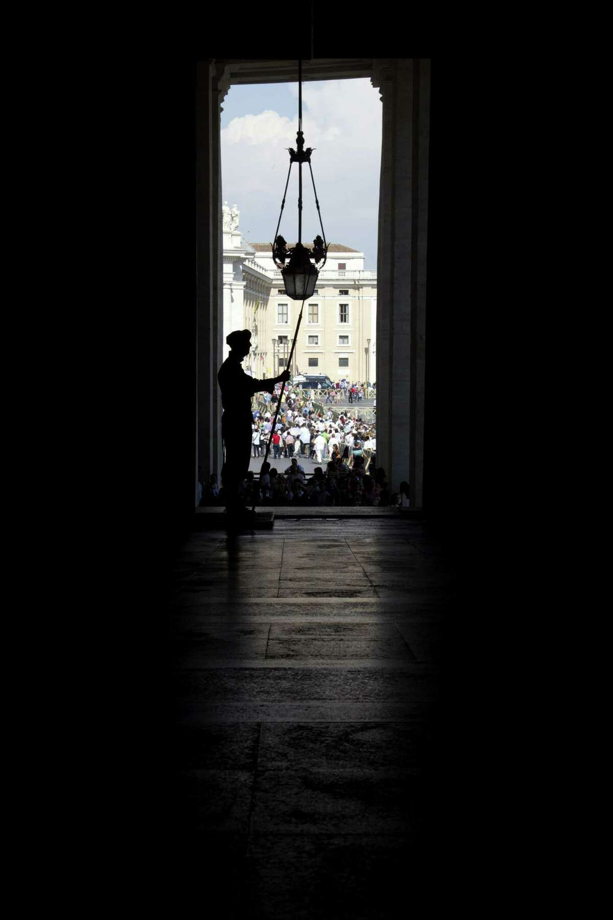 A Swiss guard is silhouetted against the crowd as he stands guard at the Vatican prior to the arrival of Russia President Vladimir Putin for a private audience with Pope Francis, Wednesday, June 10, 2015. Russian President Vladimir Putin was meeting Wednesday with Italian officials and Pope Francis as the U.S. sought to encourage the Vatican to join the West in condemning Moscow's actions in Ukraine. (AP Photo/Andrew Medichini)