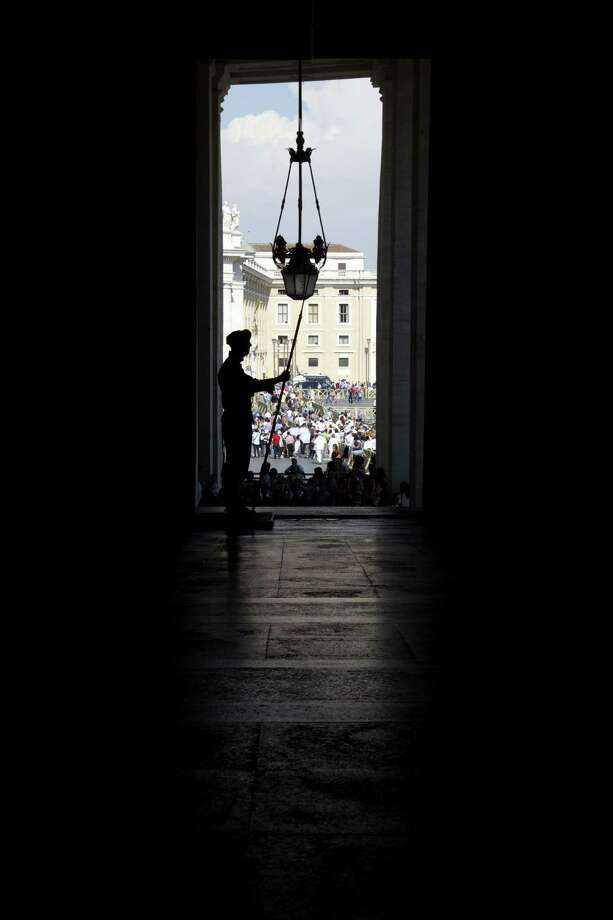 A Swiss guard is silhouetted against the crowd as he stands guard at the Vatican prior to the arrival of Russia President Vladimir Putin for a private audience with Pope Francis,  Wednesday, June 10, 2015. Russian President Vladimir Putin was meeting Wednesday with Italian officials and Pope Francis as the U.S. sought to encourage the Vatican to join the West in condemning Moscow's actions in Ukraine. (AP Photo/Andrew Medichini) Photo: AP / AP