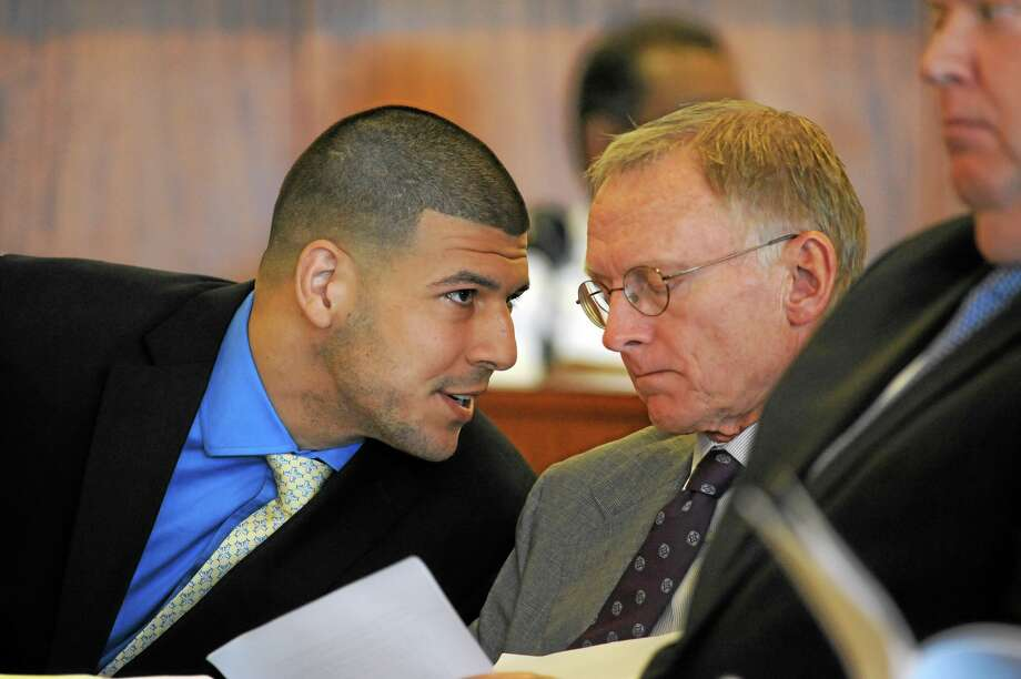 Former New England Patriots NFL football player Aaron Hernandez, left, talks with one of his defense attorneys, Charles Rankin, during a hearing at the Bristol County Superior Court House, Monday, June 16, 2014, in Fall River, Mass. Hernandez's attorneys challenged the evidence in one of his murder cases, arguing at a pretrial hearing that prosecutors have not established probable cause in the fatal shooting of Odin Lloyd. (AP Photo/Faith Ninivaggi, Pool) Photo: AP / Pool EPA