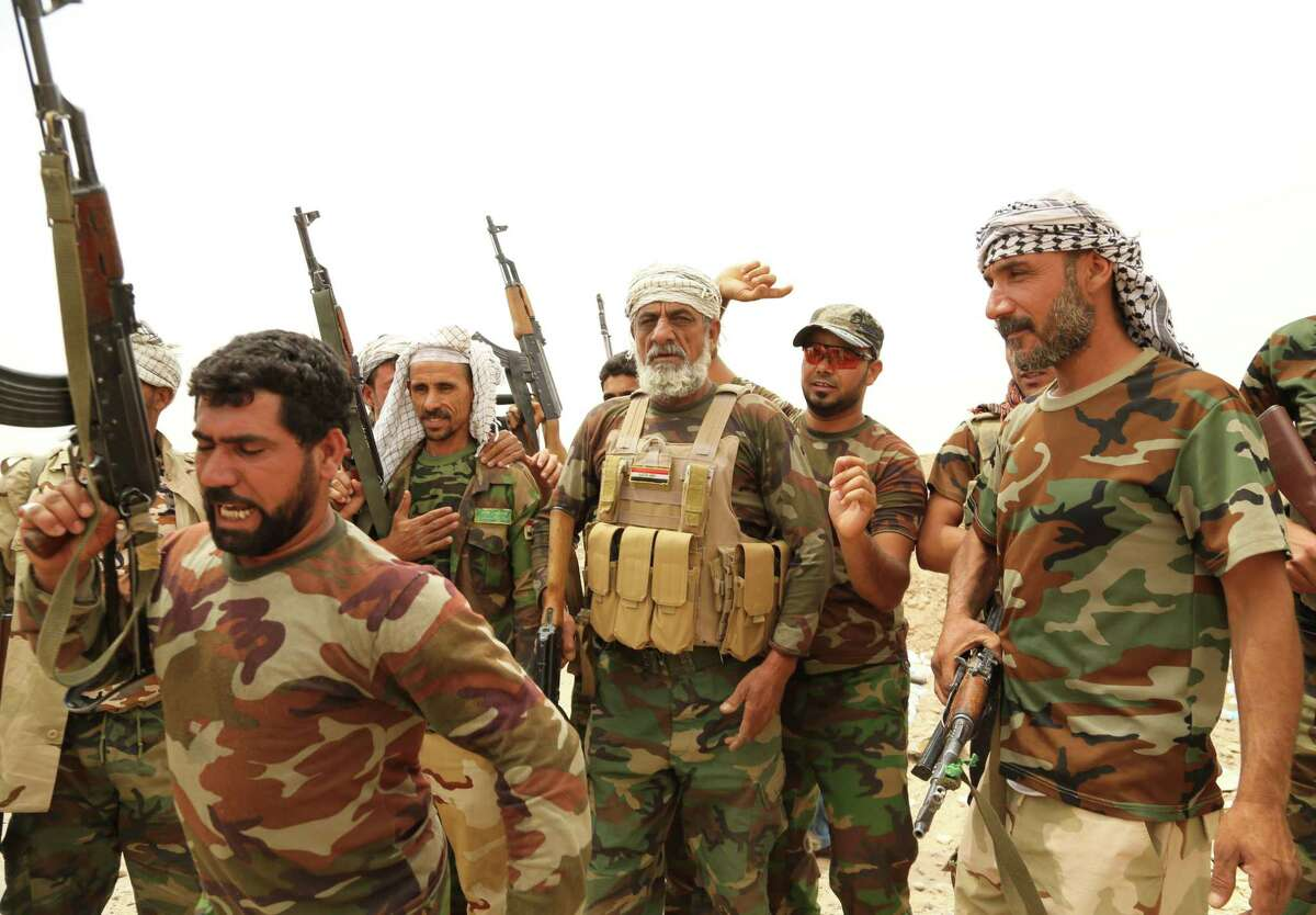 On June 1, fighters of Badr Brigades Shiite militia chant slogans against the Islamic State group at the front line on the outskirts of Fallujah, Anbar province, Iraq.