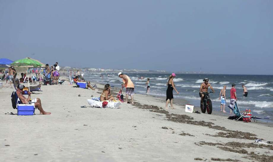 Vacationers relax on the bench and in the surf in Oak Island, N.C., Monday, June 15, 2015. A 12-year-old girl from Asheboro lost part of her arm and suffered a leg injury, and a 16-year-old boy from Colorado lost his left arm about an hour later and 2 miles away in two separate shark attacks late Sunday afternoon. (AP Photo/Chuck Burton) Photo: AP / AP