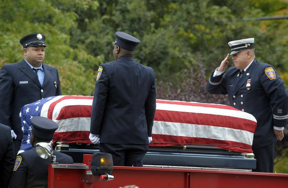 Hartford firefighters prepare take the casket from the hose bed of Engine 16 Monday during the funeral for Hartford Firefighter Kevin Bell at the First Cathedral in Bloomfield. Bell was killed in a house fire Oct. 7. Photo: The Associated Press — Journal Inquirer, Jim Michaud, Pool  / Pool Journal Inquirer