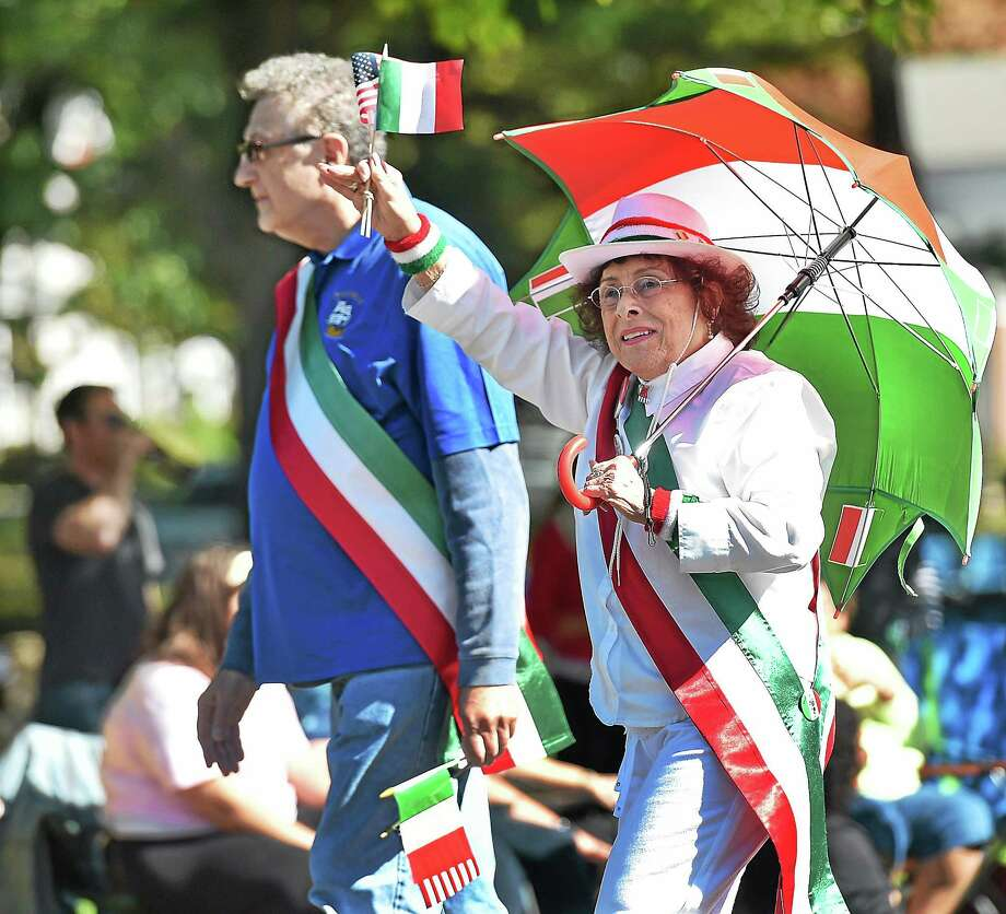 Catherine Avalone -- New Haven Register Carrying a red, white and green umbrella, Madeline Carrone of New Haven waves the American and Italian flags to the crowd marching down Church Street in North Haven during the annual Columbus Day Parade on Oct. 13, 2004. Photo: Journal Register Co. / New Haven RegisterThe Middletown Press