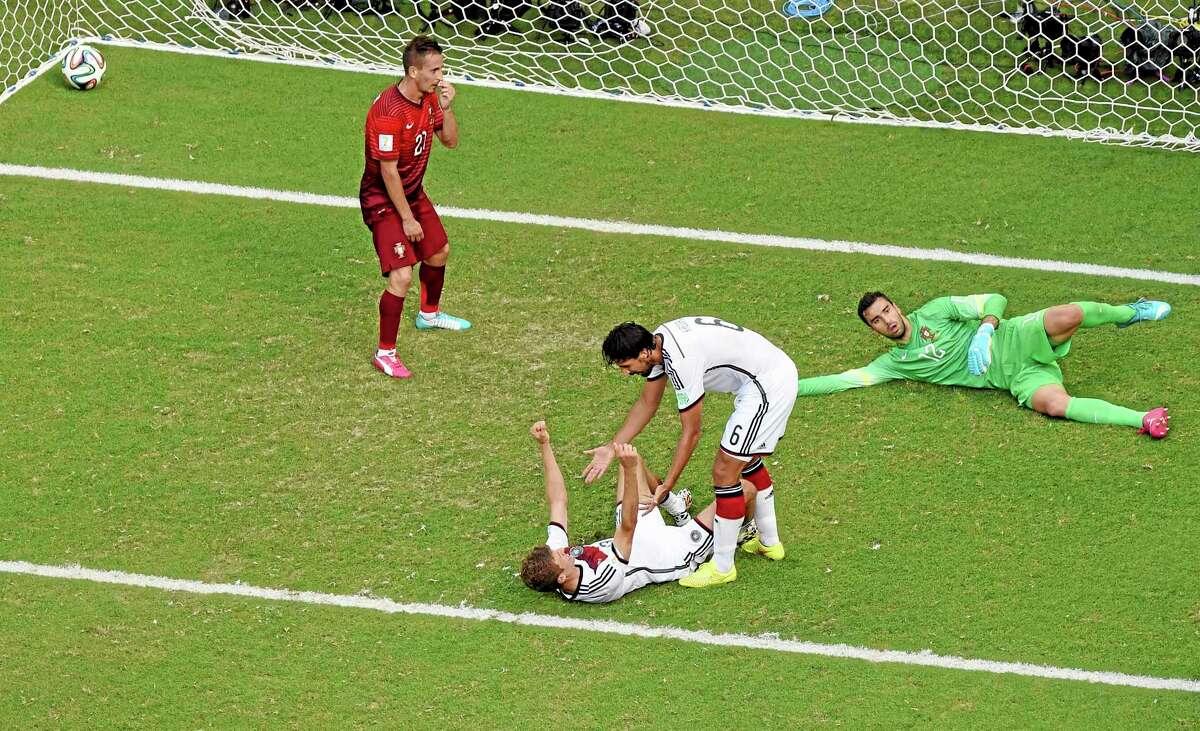Germany's Thomas Mueller, bottom, celebrates with teammate Sami Khedira after scoring their fourth goal Monday.