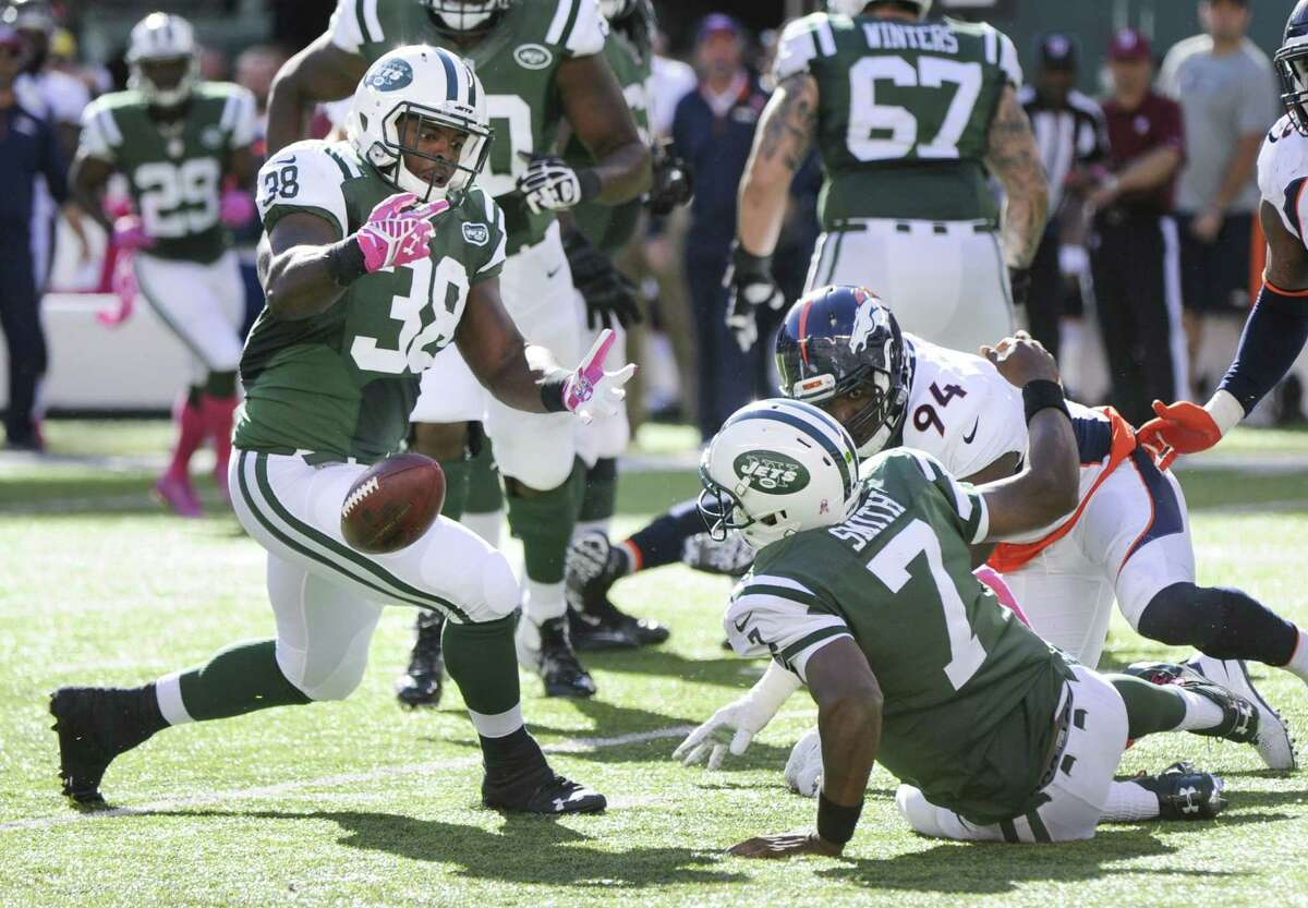 Jets quarterback Geno Smith (7) fumbles the ball as he attempts to pass it off to running back John Conner on Sunday.