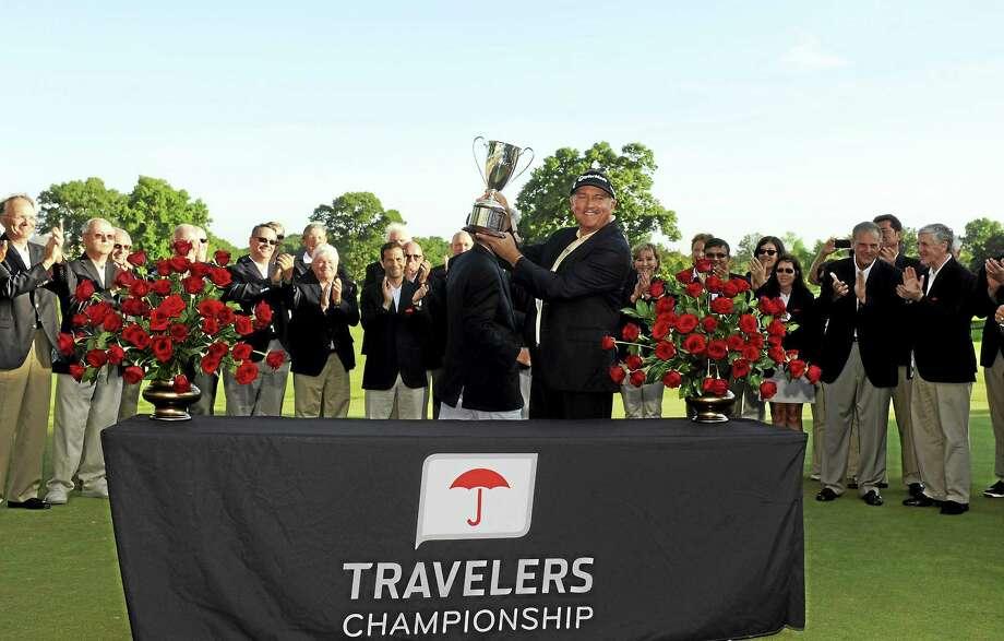 Ken Duke raises the trophy after winning the Travelers Championship last year. Photo: Fred Beckham — The Associated Press  / FR153656 AP