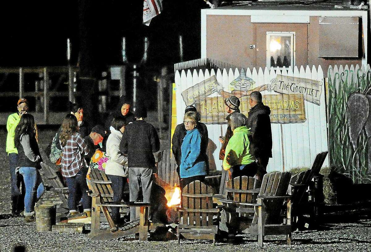 People gather around a fire at Harvest Hill Farms after a hayride accident that injured multiple people on Oct. 11, 2014 in Mechanic Falls, Me. Police in Maine confirm a teen has died and two remain in critical condition after the crash. At least 20 other passengers were taken to area hospitals for treatment.