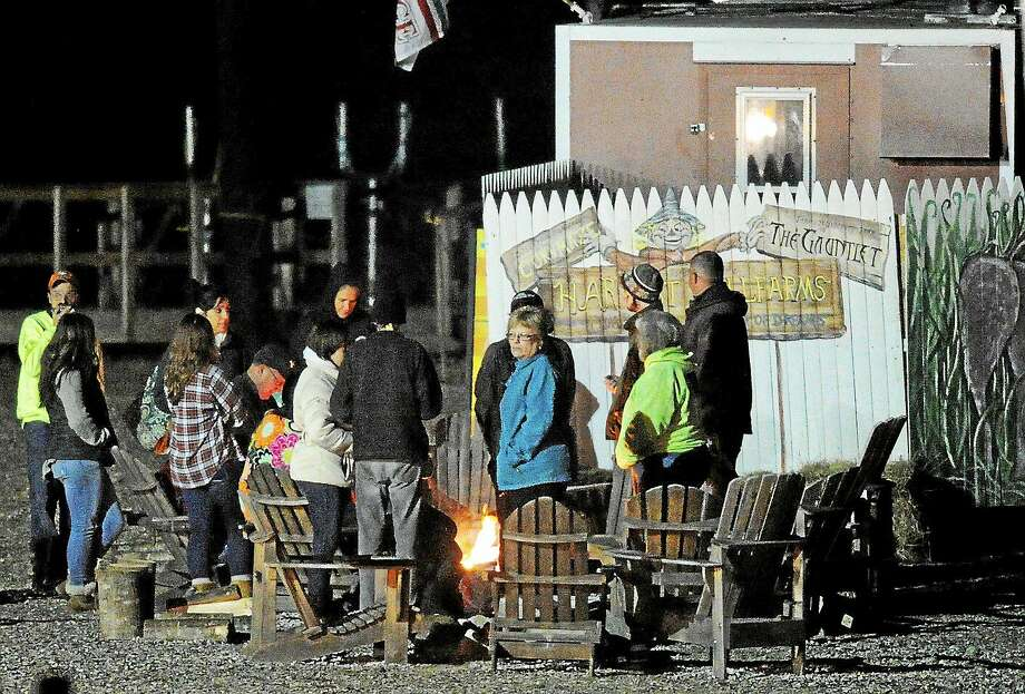 People gather around a fire at Harvest Hill Farms after a hayride accident that injured multiple people on Oct. 11, 2014 in Mechanic Falls, Me. Police in Maine confirm a teen has died and two remain in critical condition after the crash. At least 20 other passengers were taken to area hospitals for treatment. Photo: AP Photo/Maine Today, Gabe Souza  / Maine Today/The Portland Press Herald