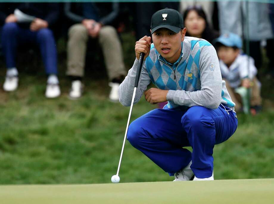 International team player Sangmoon Bae of South Korea lines up his putt on the 13th hole Saturday. Photo: Lee Jin-man — The Associated Press  / AP