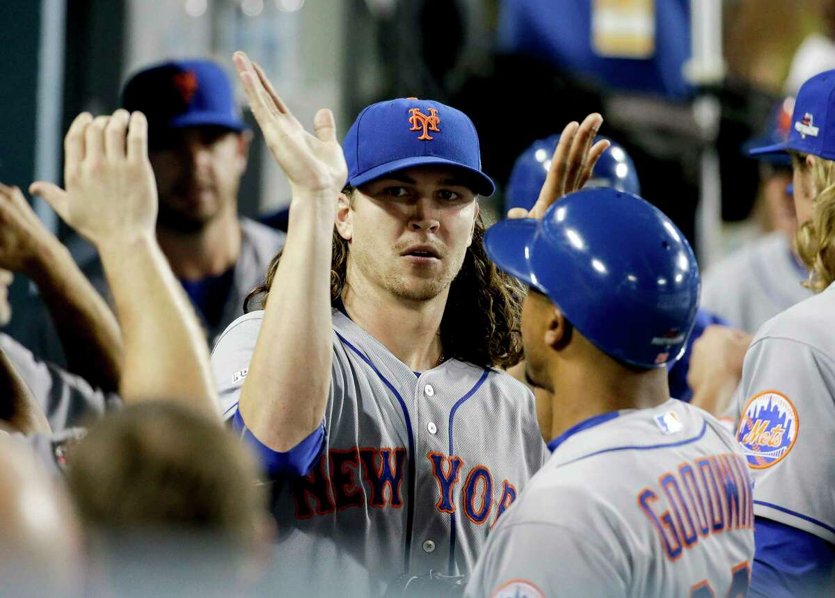 Mets starting pitcher Jacob deGrom celebrates in the dugout the end of the seventh inning Friday night.
