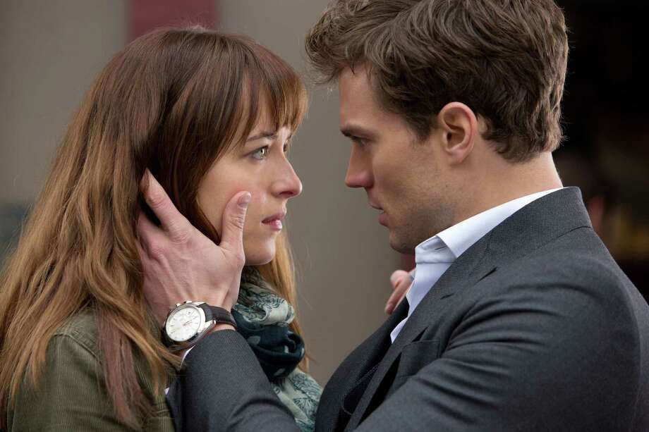 """In this image released by Universal Pictures and Focus Features, Dakota Johnson, left, and Jamie Dornan appear in a scene from """"Fifty Shades of Grey."""" (AP Photo/Universal Pictures and Focus Features) Photo: AP / Universal Pictures and Focus Features"""