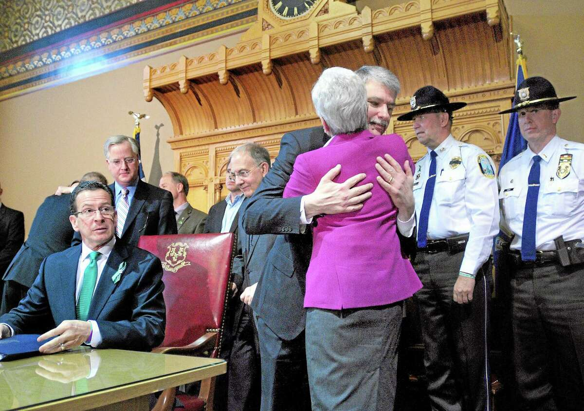 Gov. Dannel P. Malloy, left, watches Senate President Pro Tempore Donald E. Williams Jr., right, hug Lt. Gov. Nancy Wyman after the signing of the Gun Violence Prevention and Child Safety Act at the Capitol in Hartford on April 4, 2013.