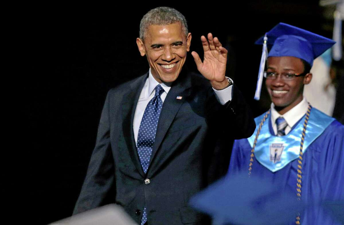 President Obama, followed by student body President Reginald Sarpong, waves to students as he arrives for the graduation ceremony for Worcester Technical High School, Wednesday, June 11, 2014, in Worcester, Mass. Afterward he will attend a democratic fundraiser in Massachusetts, before returning to Washington. (AP Photo/Charles Krupa)