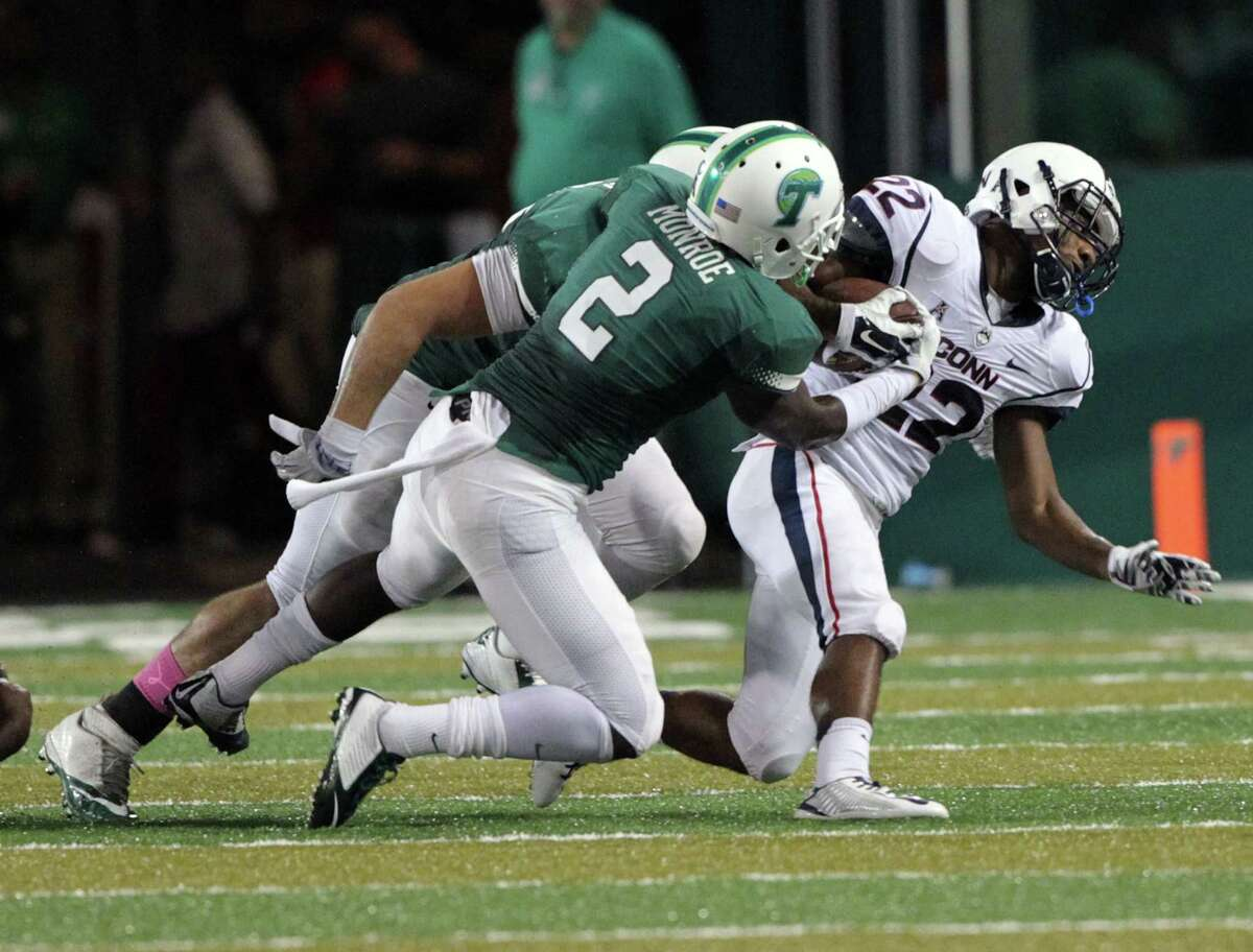 Tulane safety Darion Monroe forces a fumble from UConn running back Arkeel Newsome during Saturday's game in New Orleans.