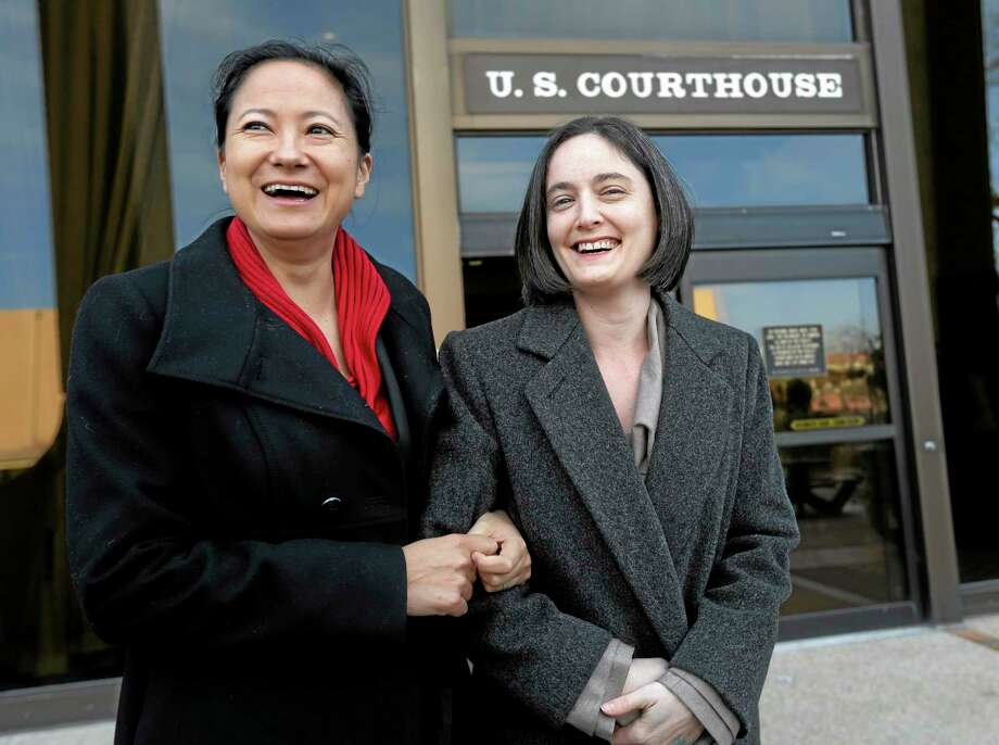 File - In this Feb. 12, 2014 file photo, Cleopatra De Leon, left, and partner, Nicole Dimetman, right, arrive at the U.S. Federal Courthouse, in San Antonio, where a federal judge is expected to hear arguments in a lawsuit challenging Texas' ban on same-sex marriage. On Wednesday, Feb. 26, 2014, Judge Orlando Garcia has struck down  the ban but is leaving it in place pending a ruling by an appeals court later this year. (AP Photo/Eric Gay, File) Photo: AP / AP