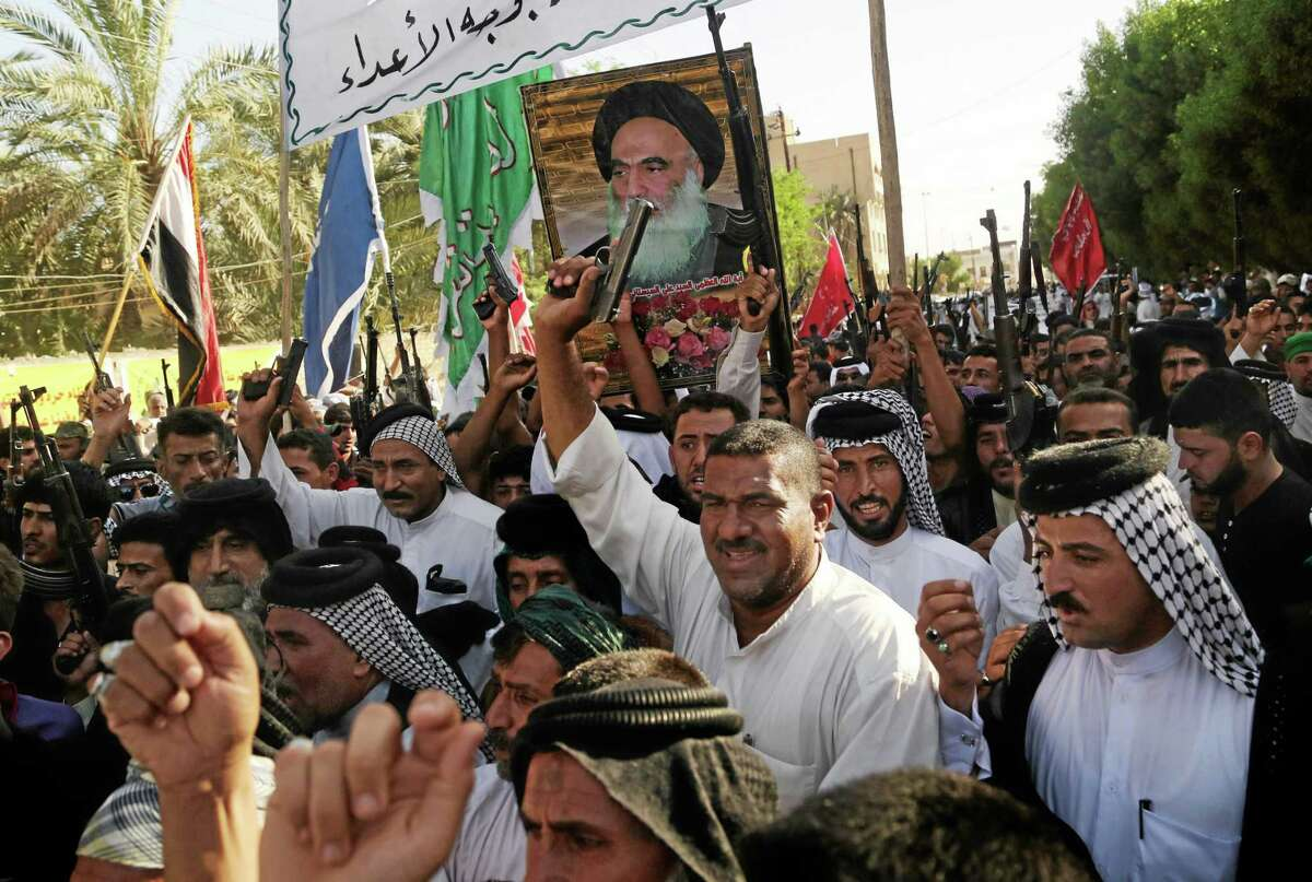 Shiite tribal fighters carry a poster of Shiite spiritual leader Grand Ayatollah Ali al-Sistani, as they raise their weapons chanting against the al-Qaida-inspired Islamic State of Iraq and the Levant (ISIL) in Basra, Iraq's second-largest city, 340 miles (550 kilometers) southeast of Baghdad, Iraq, Monday, June 16, 2014. Sunni militants captured a key northern Iraqi town along the highway to Syria early on Monday, compounding the woes of Iraq's Shiite-led government a week after it lost a vast swath of territory to the insurgents in the country's north. (AP Photo/ Nabil Al-Jurani)