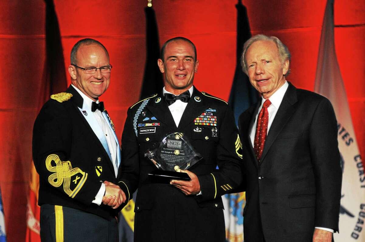 "Col. David Sutherland and Sen. Joseph Lieberman present Sgt. Joe Kapacziewski (center) with the ""No Greater Sacrifice"" Freedom Award in 2011."