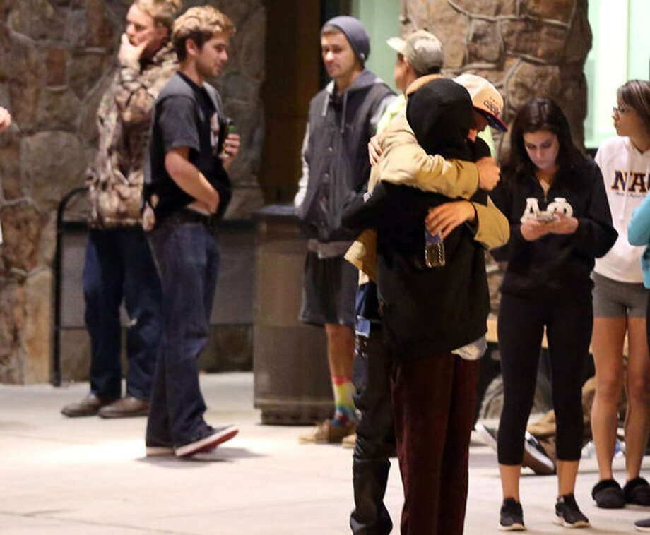 Students embrace outside a hospital emergency room in Flagstaff, Ariz., on Friday, Oct. 9, 2015, after an early morning fight between two groups of college students escalated into gunfire, leaving one person dead and three others wounded, authorities said. The shooting occurred outside a dormitory near the Northern Arizona University campus. Photo: Jake Bacon/Arizona Daily Sun Via AP   / Arizona Daily Sun