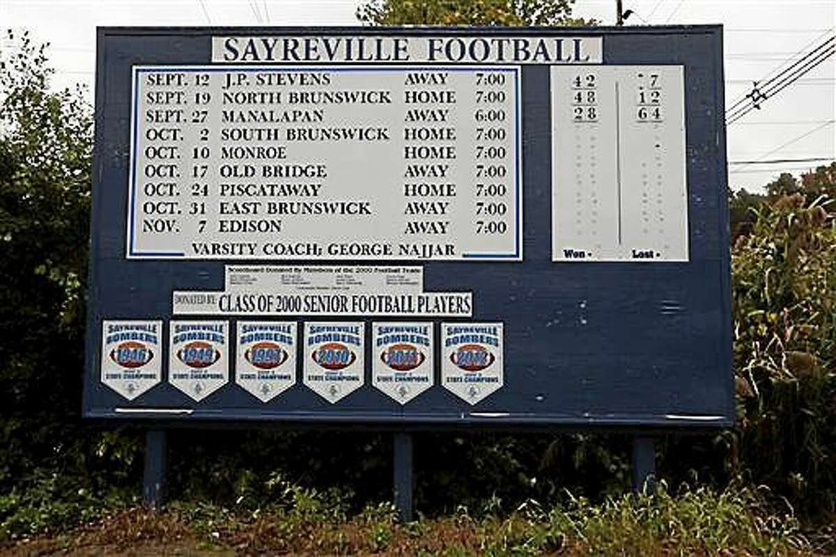 A roadside sign displays the Sayreville War Memorial High School football team schedule on Main Street in Sayreville, N.J., Saturday, Oct. 11, 2014. Seven students were charged with sex crimes in connection with a series of assaults amid an investigation into hazing by the high school football team, which already led to the cancellation of the rest of the season, authorities said. Six of the seven students, ranging in age from 15 to 17, were arrested Friday night, and the seventh was being sought, police and prosecutors said. (AP Photo/Julio Cortez)