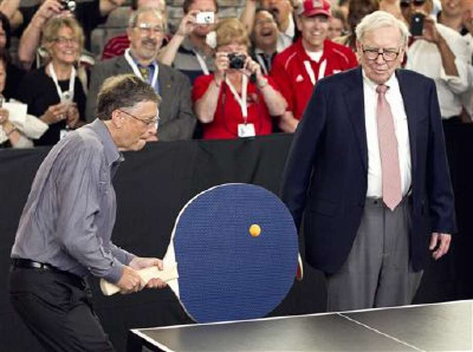 "FILE - In this May 6, 2012 file photo, Warren Buffett, chairman and CEO of Berkshire Hathaway, right, watches Bill Gates use an oversize paddle as they play doubles against table tennis prodigy Ariel Hsing in Omaha, Neb. Members of the economic elite are looking for ways to reduce the nation's growing income inequality for a variety of reasons, from self-interest to pangs of conscience. Buffet advocated for a progressive estate tax before members of Congress, saying in 2007, ""Dynastic wealth, the enemy of a meritocracy, is on the rise. Equality of opportunity has been on the decline. A progressive and meaningful estate tax is needed to curb the movement of a democracy toward plutocracy."" (AP Photo/Nati Harnik, File) Photo: AP / AP"