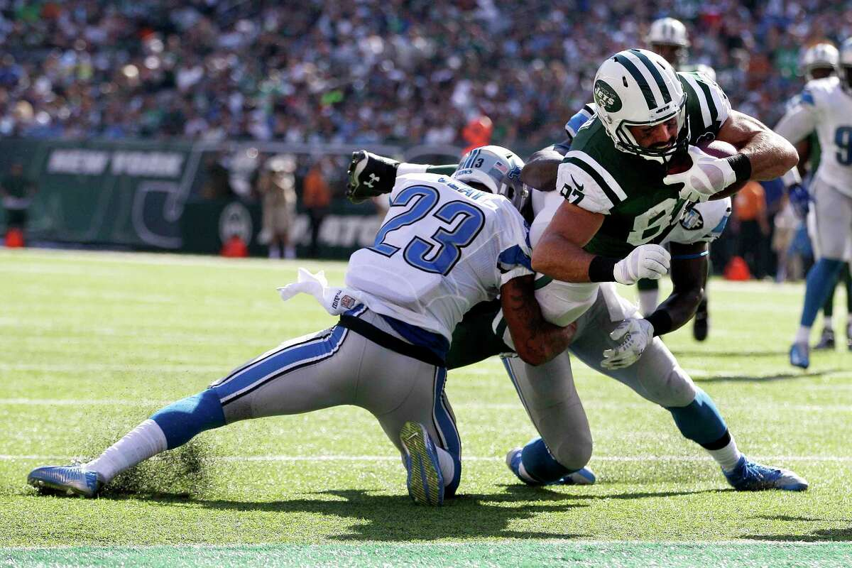 New York Jets receiver Eric Decker, center, dives in between Detroit Lions cornerback Darius Slay, left, and linebacker Tahir Whitehead for a touchdown on Sept. 28 in East Rutherford, N.J.